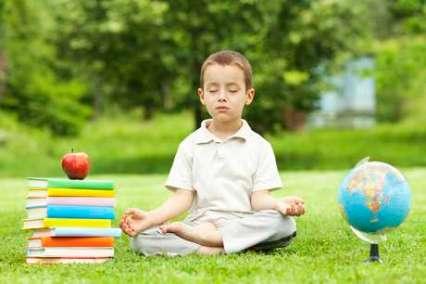 Little boy in zen meditation preparing to be good student